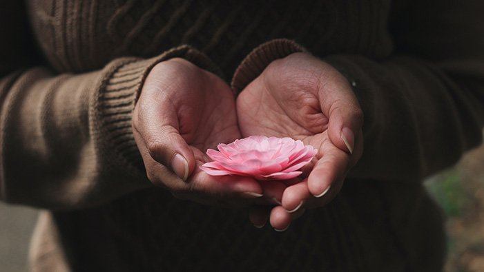 Woman holding delicate flower.