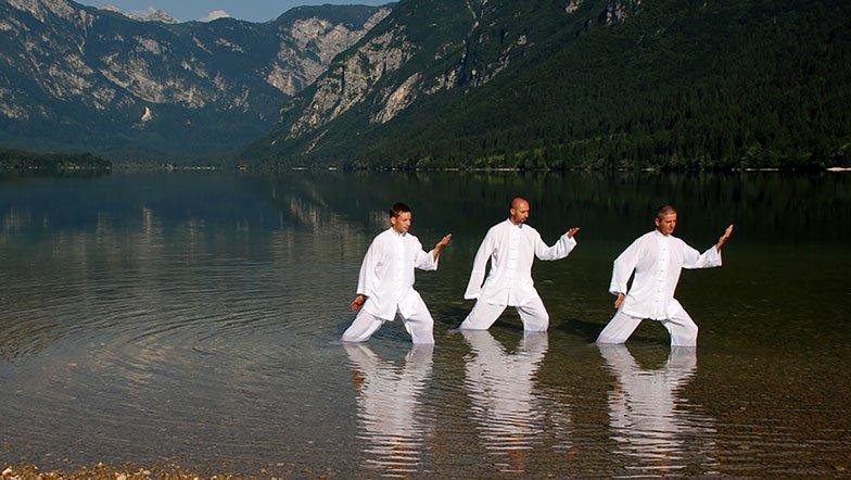 Men practising Tai Chi and Qi Gong by shores of mountain lake.