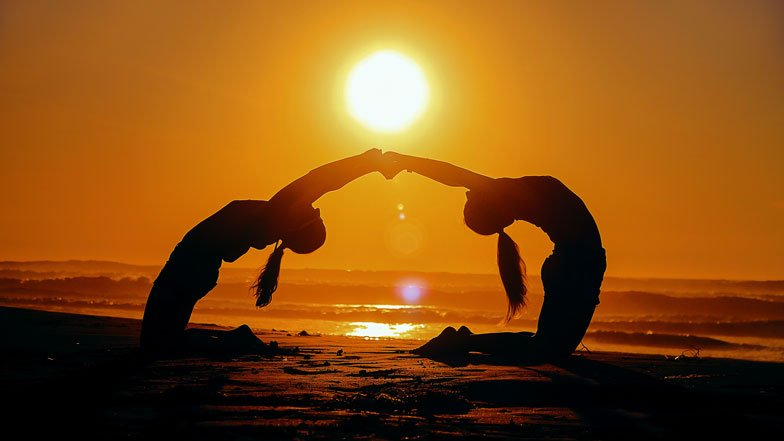 Two women doing yoga by the sea at sunset.
