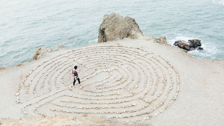 Woman walking in labyrinth made of stone pebbles by the sea.