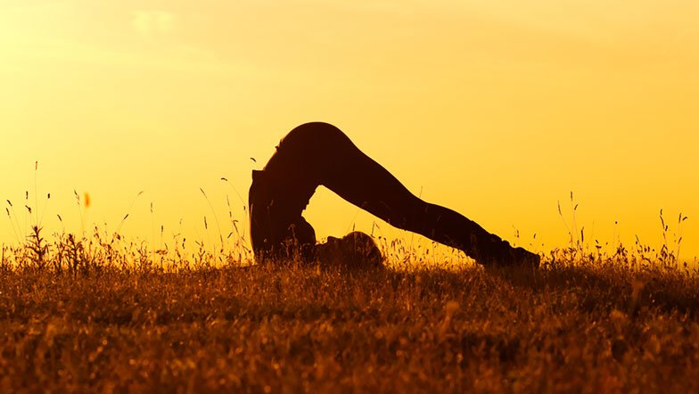 Woman practises Yoga on grass at sunset.