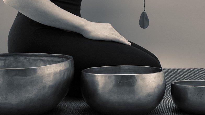 Woman kneeling behind 3 Meditation Bowls