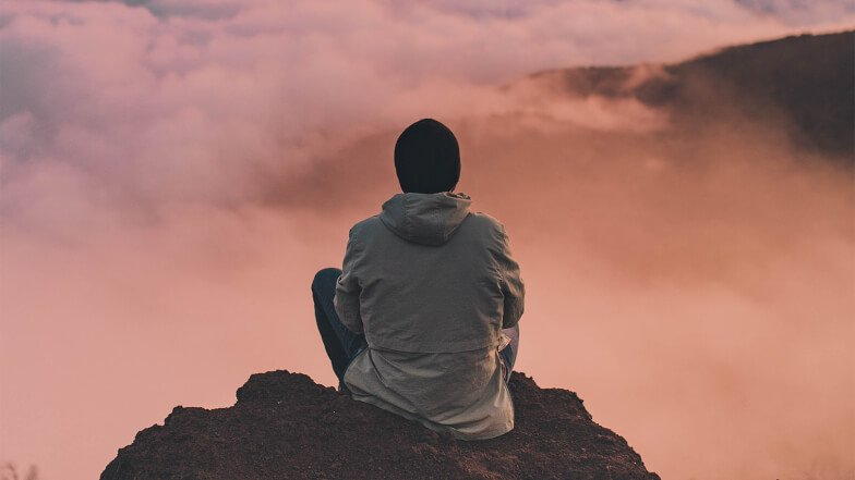 Man meditating on rock overlooking clouds.