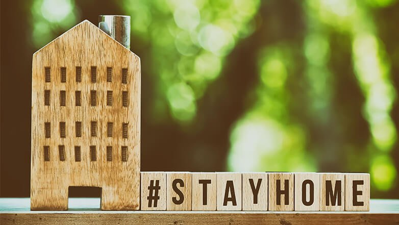 A wooden model of apartments with building blocks arranged to spell #stayhome.