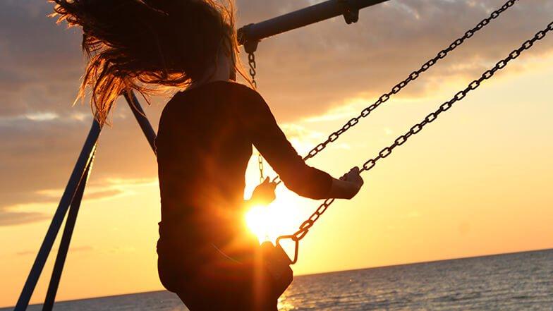 Joyful Mindfulness - Woman swinging beside the sea at sunset