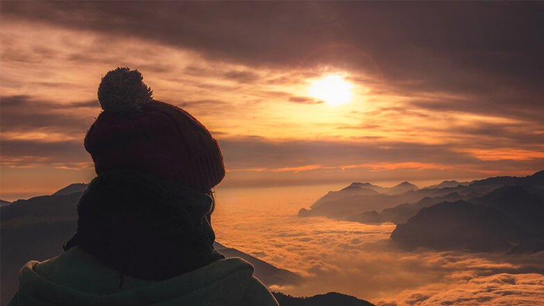 Woman watching the sunset from above the clouds.